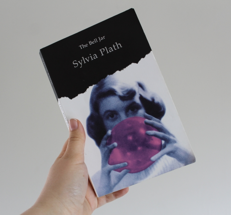 Black and white cover of The Bell Jar, with a girl blowing a pink bubble