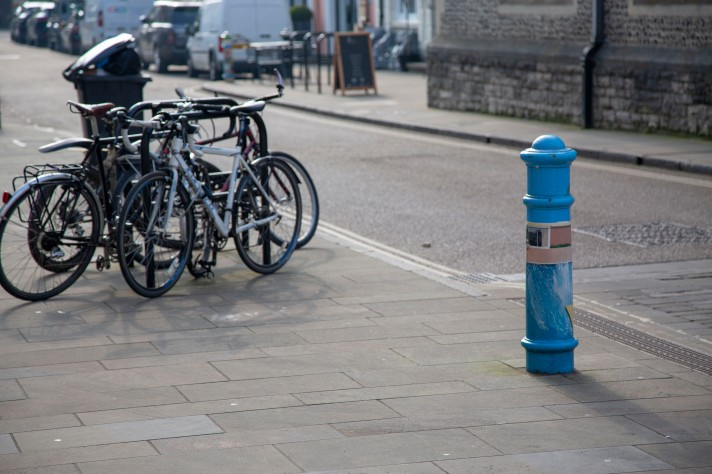 A picture focusing on a bollard painted in the style of David Hockney's 'A Bigger Splash', with bikes in the background