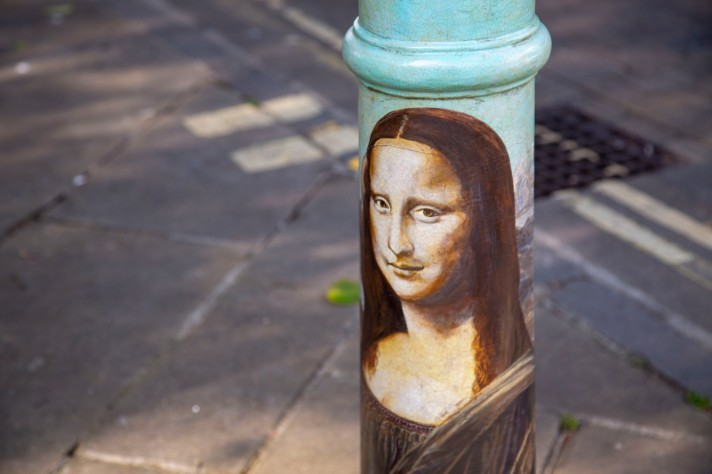 A bollard painted in the style of Da Vinci's 'The Mona Lisa'