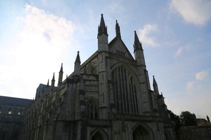 The front of Winchester Cathedral, against a cloudy blue sky