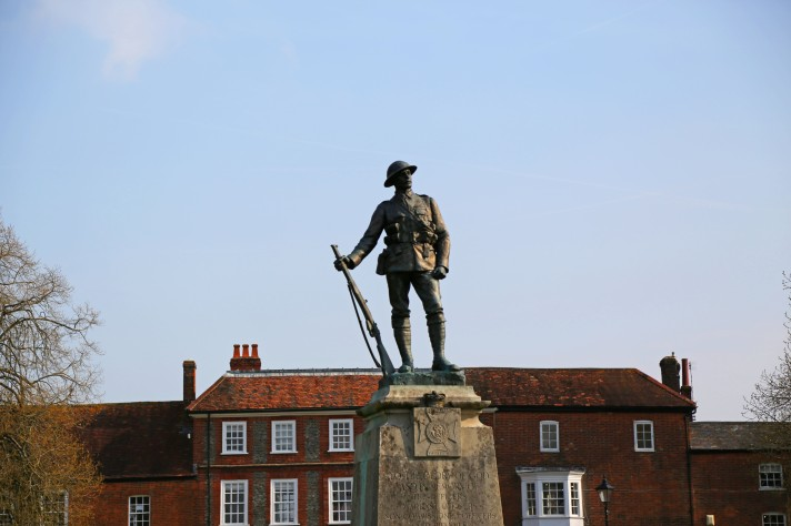 A statue commemorating soldiers from WW1 and WW2 against a blue sky