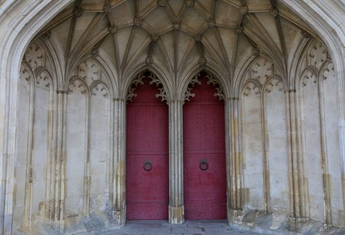 Two aged red doors that lead into Winchester Cathedral