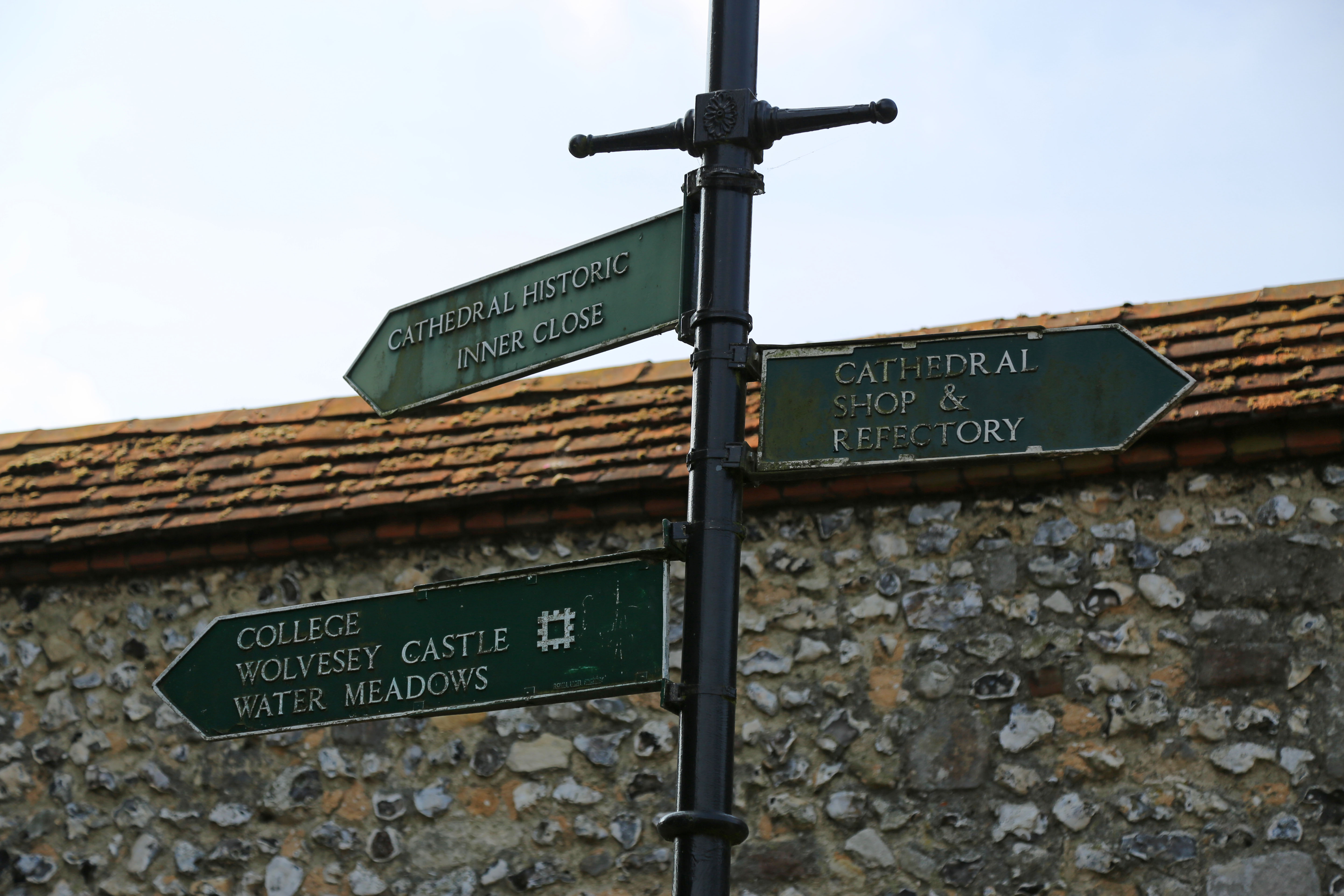 Three green signs pointing to various places around the catheral.
