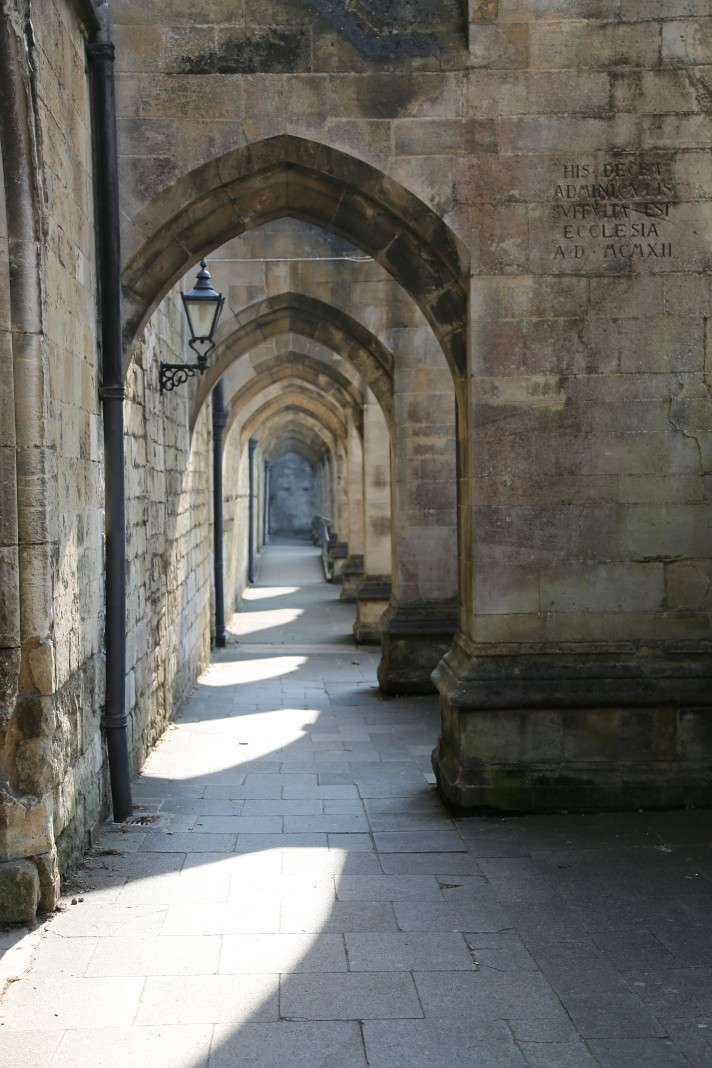 Arches cover a walkway that run adjacent to Winchester Cathedral, the sun causing shapes on the ground