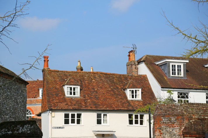 Focus on the white washed houses on Minster Street against a blue sky