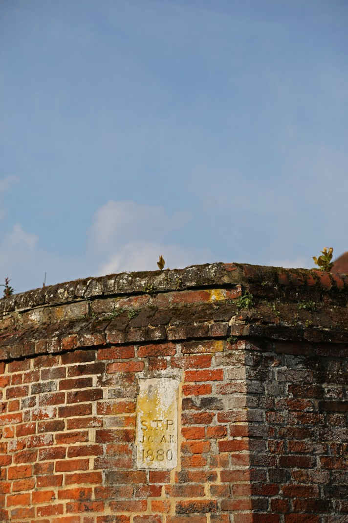 Corner of a wall, with eh year 1880 inscribed, against a blue sky