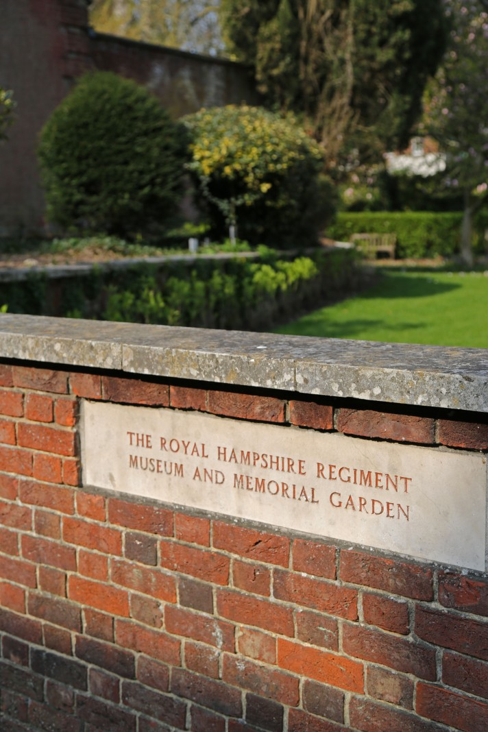 Focus on a red brick wall with the words 'The Royal Hampshire Regiment Museum & Memorial Garden' inscribed, with the garden in the background