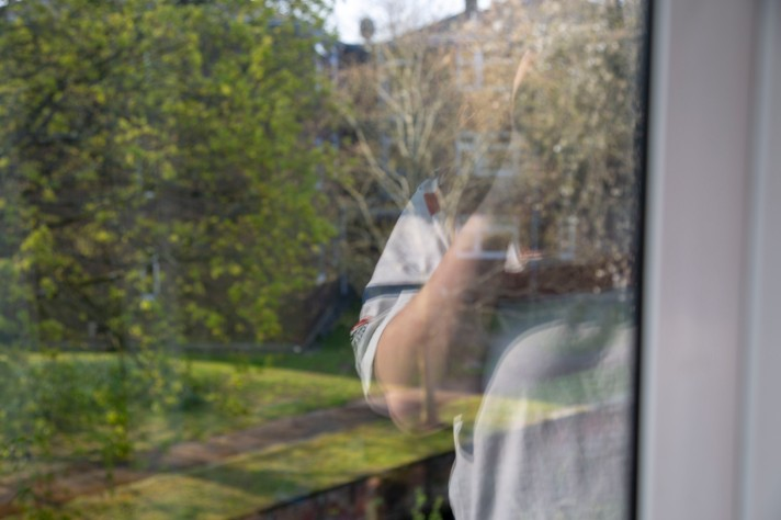 A picture of a window - in the background are trees, and in the foreground is Rosie's torso in a white pajama top