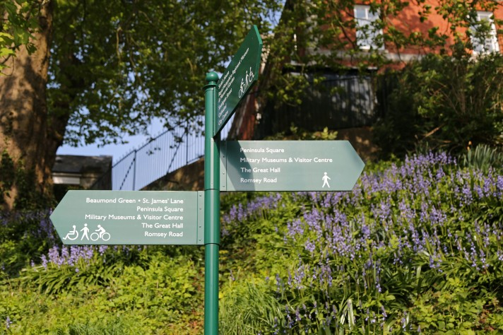 Three signs pointing to the historical landmarks at Winchester Barracks, with blue flowers in the background