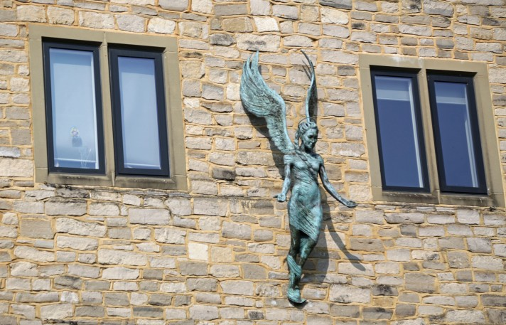 Statue of an angel in between two windows - the angel is blue and weather-warn