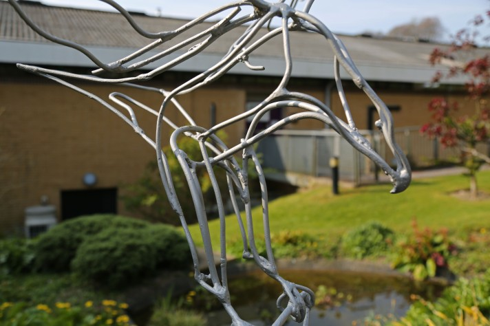 Statue of a wire silver eagle, with a pond and greenery in the background