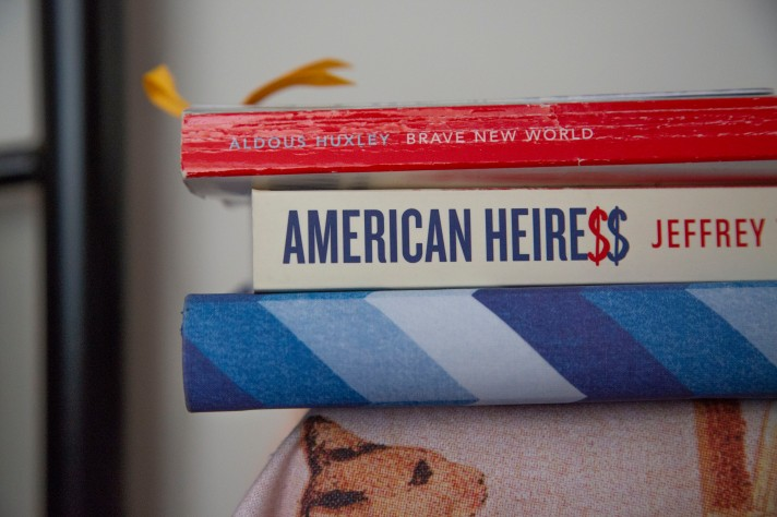 A picture of the corner of Rosie's bedside table, including 'Brave New World' by Aldous Huxley, 'American Heiress' by Jeffrey Toobin, and Rosie's diary