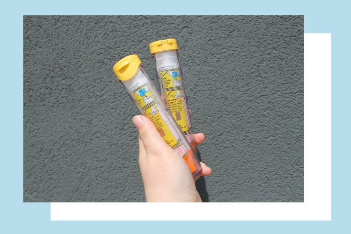 Rosie's hand holding two Epipens against a grey wall