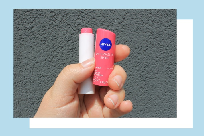 Rosie's hand holding the pink packaging of Nivea's Watermelon Shine lipbalm against a grey background