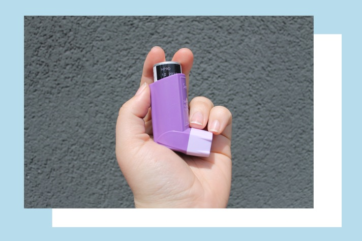 Rosie's hand holding a purple Seretide inhalers against a grey background