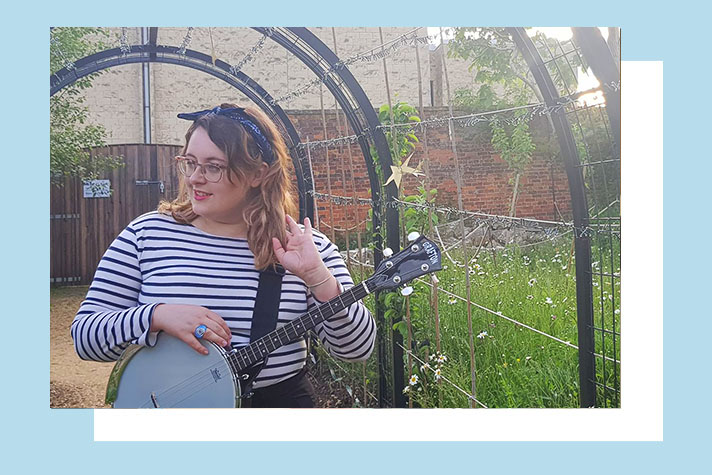 Rosie Lewis with her tenor banjo in a garden