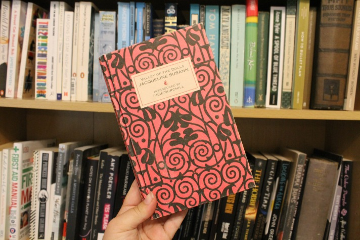 Pink cover of Susann's 'Valley of the Dolls' against a bookshelf