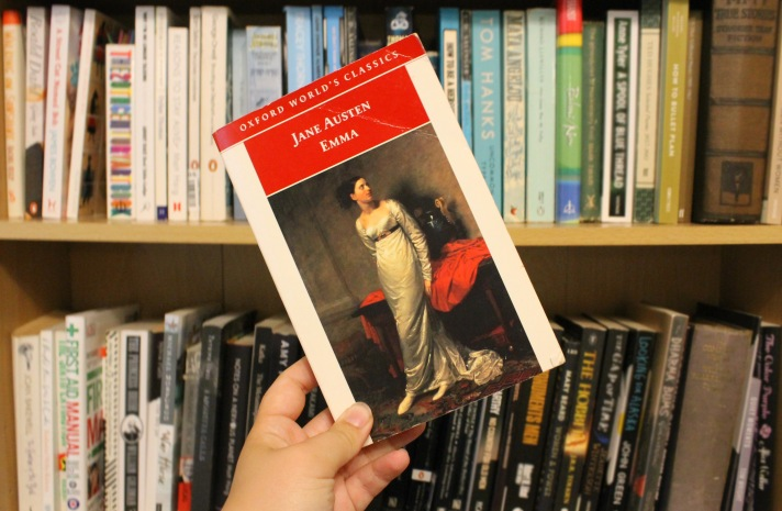 Cover of Jane Austen's 'Emma' in front of a bookshelf. The cover shows a picture of a young woman looking in the distance
