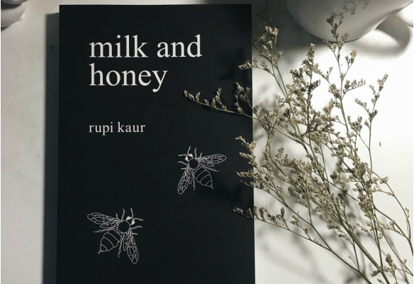 Black cover of Rupi Kaur's 'Milk & Honey' with some wildflowers