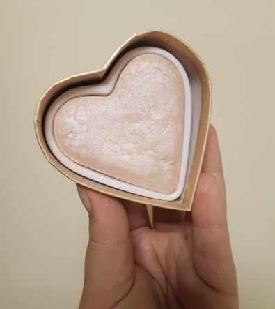Rosie's hand holding up a gold coloured highlighter in a heart shaped pan