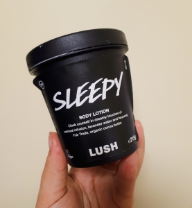 Rosie's hand holding a black pot of Lush's Sleepy