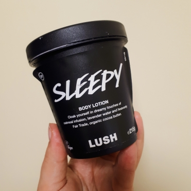 Rosie's hand holding a black pot of Lush's Sleepy
