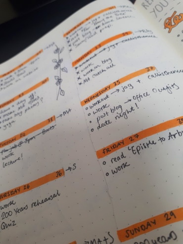 Photo from Rosie's bujo of a bright orange weekly spread, with notes in black ink
