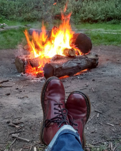 Cherry red Doc Martens against an open fire pit