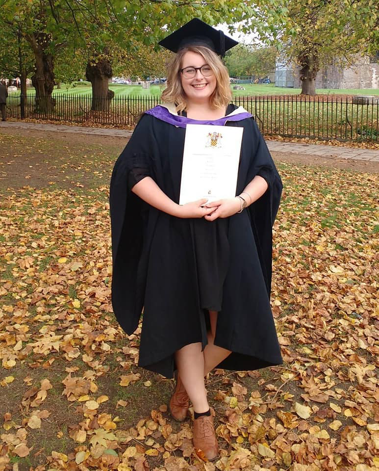 A picture of Rosie wearing her graduand robe, whilst holding her degree papers, against an autumnal backdrop