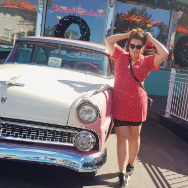 Rosie stood outside Mel's Drive in at Universal Studios. She is wearing a red tea dress form ASOS
