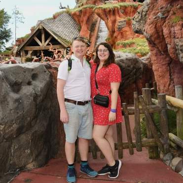 Rosie and her partner Rory stood in front of Splash Mountain ride. Rosie is wearing a read tea dress from ASOS