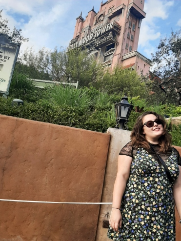 ROsie stood in front of the Tower of Terror, wearing a black and floral swing dress from ASOS, paired with a mesh top
