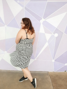 Rosie wearing a black and white checked midi dress against the famous Purple Wall in Magic Kingdom