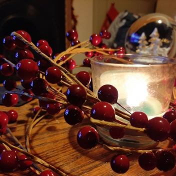 Red cranberry wreath surrounding a lit candle