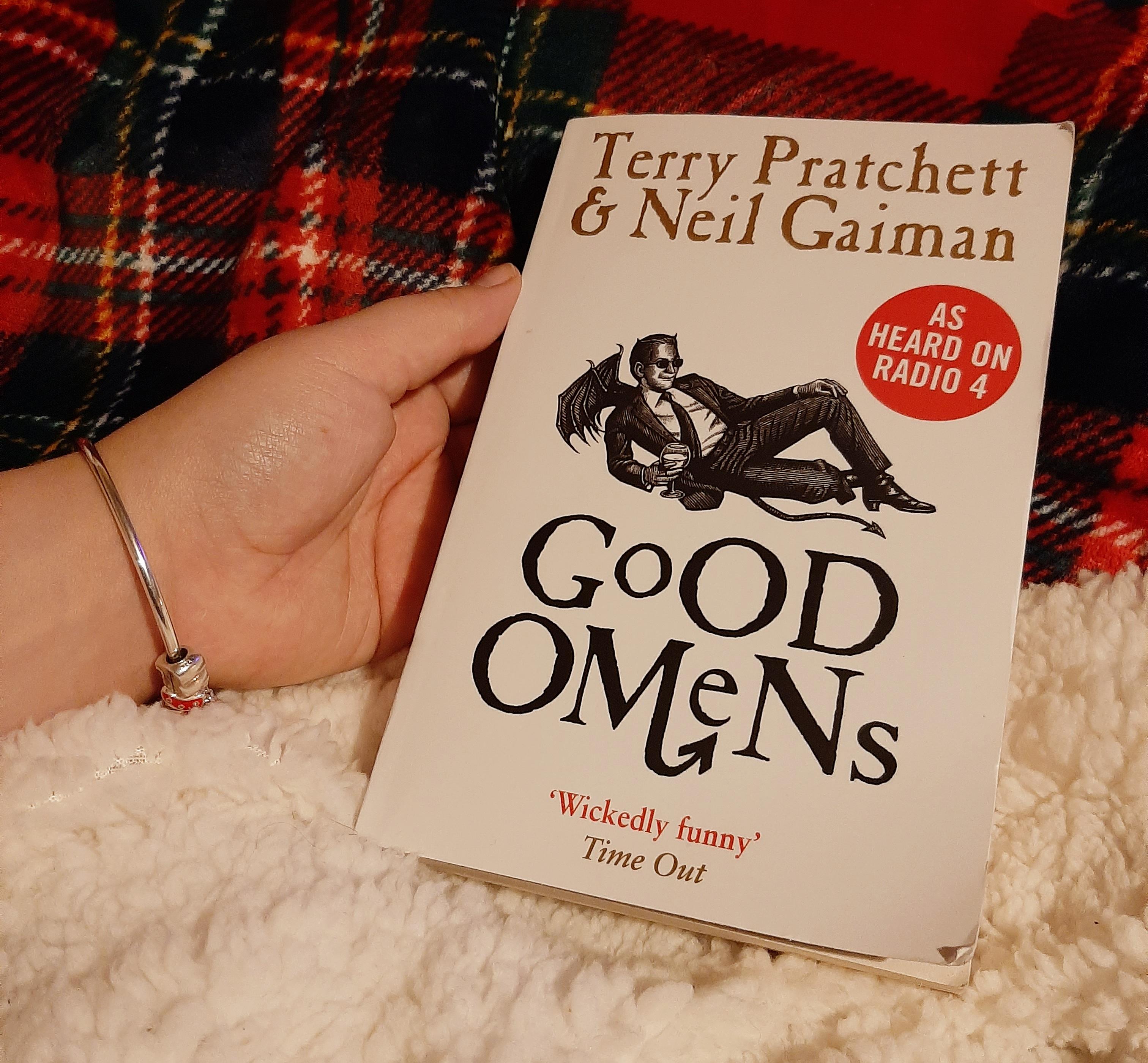 Pratchett and Gaiman's novel 'Good omens' against a checkered red blanket backdrop