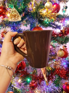 Rosie holding up her favourite mug against the backdrop of a lit Christmas tree