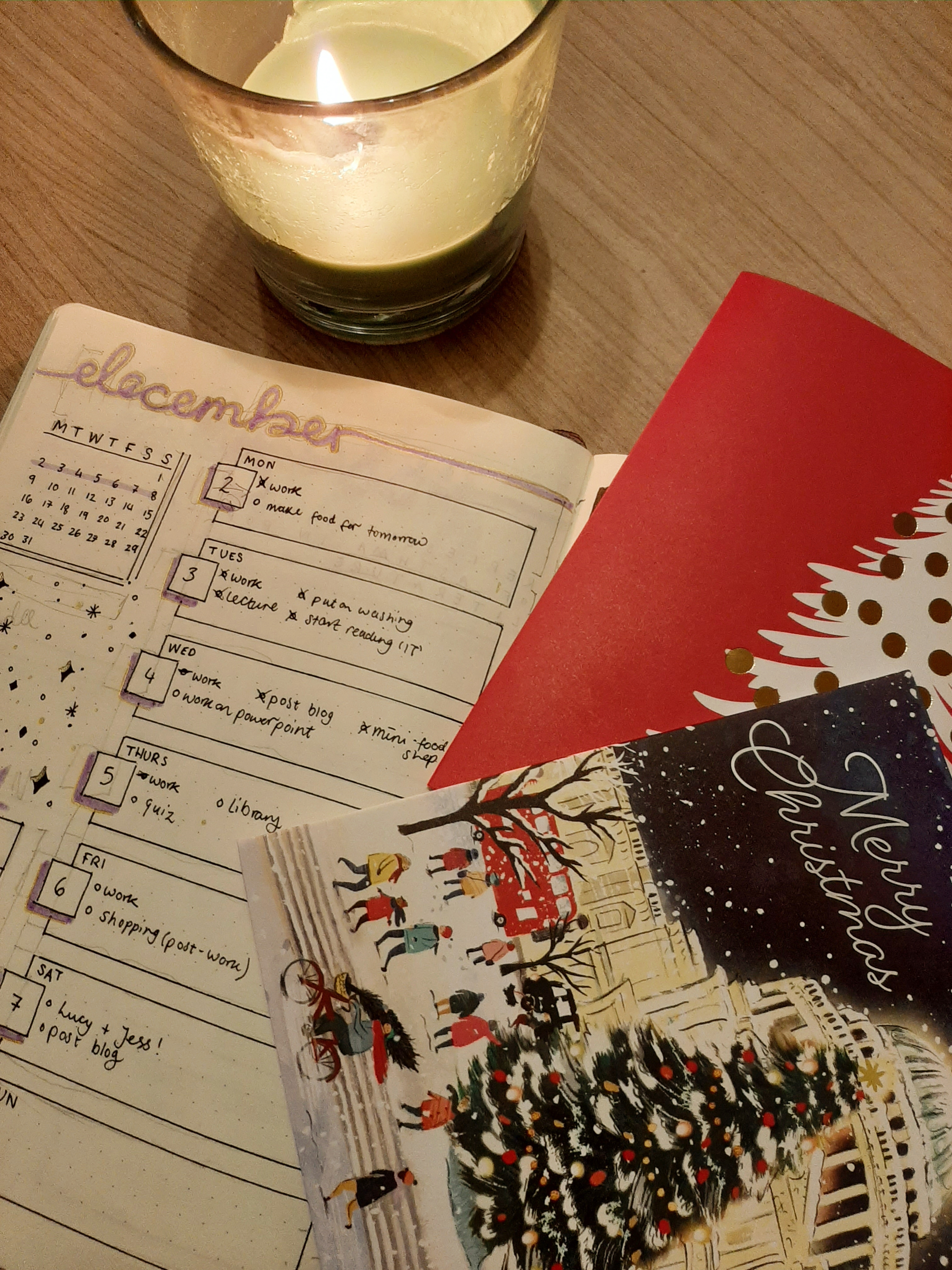 Christmas cards & bullet journaling, with a lit candle