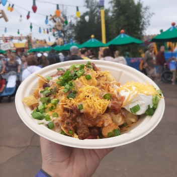 Rosie's hand holding up a bowl of totchos with Toy Story Land in the background
