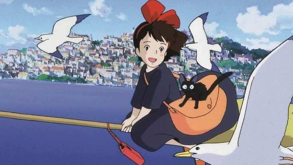 Kiki on her broom flying over a seaside city with three gulls