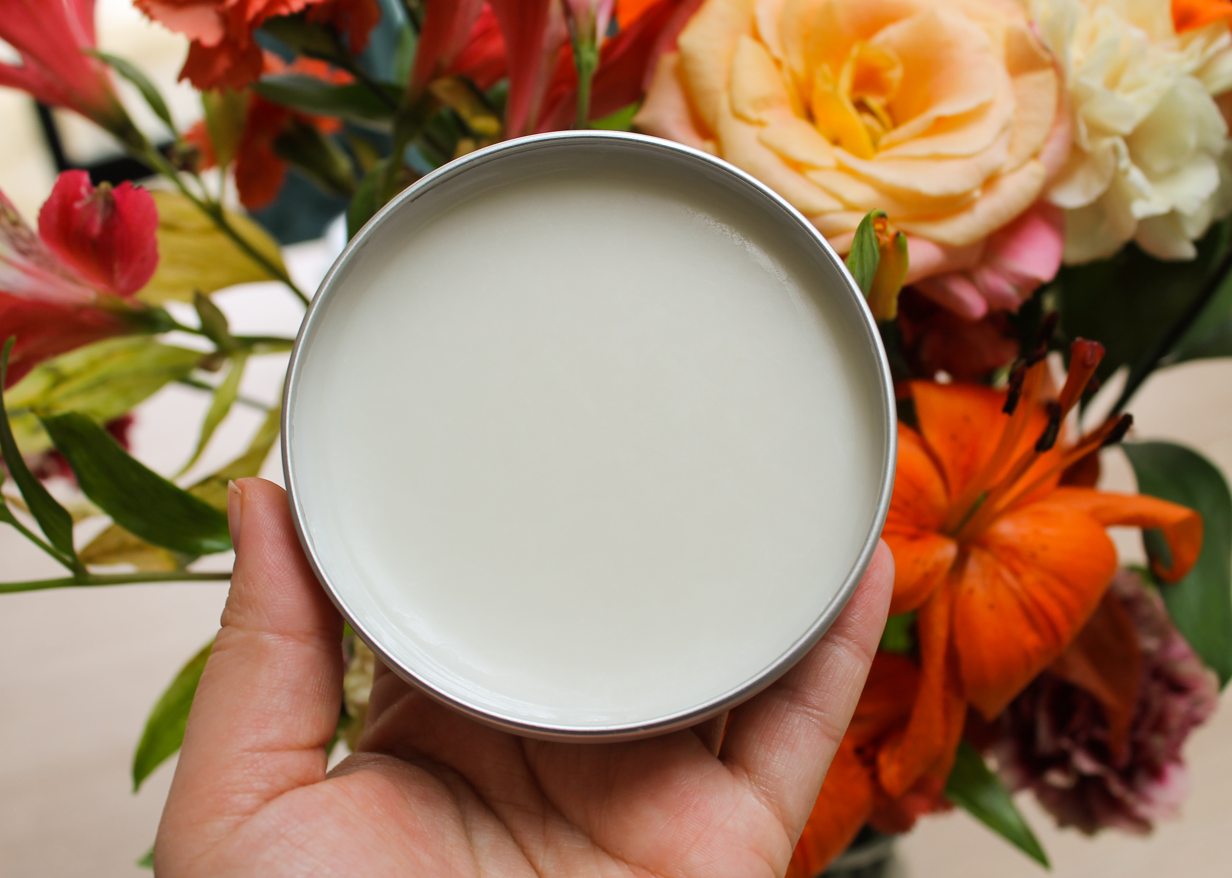Open tin of Camomile Cleansing Butter against a bouquet of flowersmile Cleansing Butter against a bouquet of flowers