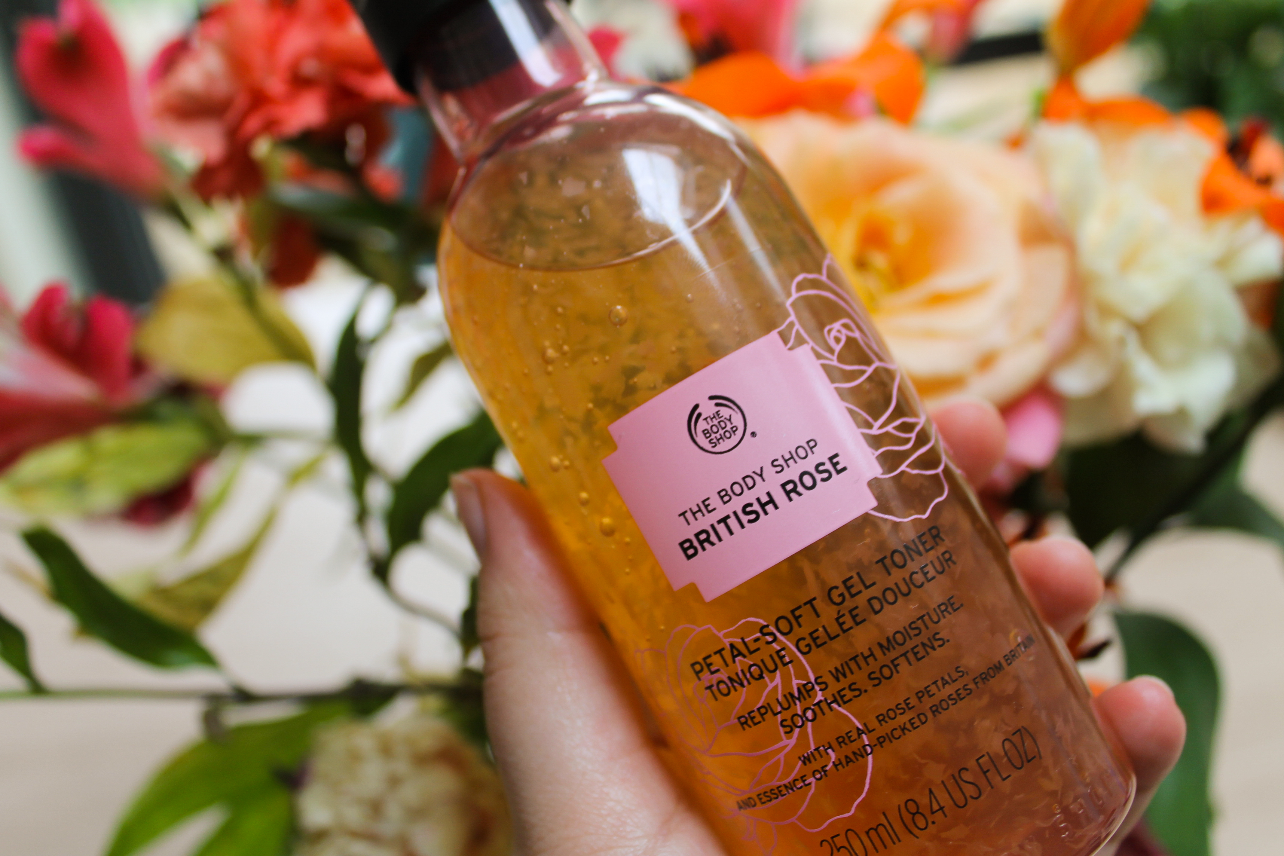 Close up of Rose Petal Toner in front of bouquet of flowers