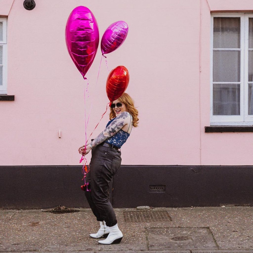 Helen holding red and pink heart shaped balloons against a pink wall