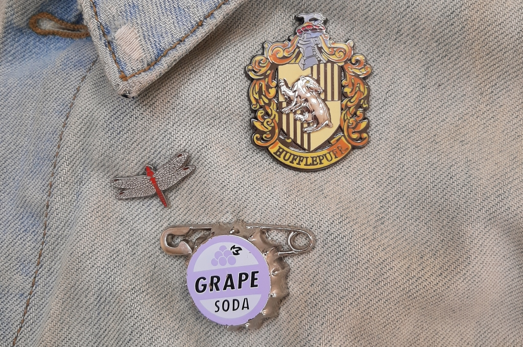 Close up of Rosie's light denim jacket with a dragonfly pin, Grape Soda badge, and Hufflepuff crest.