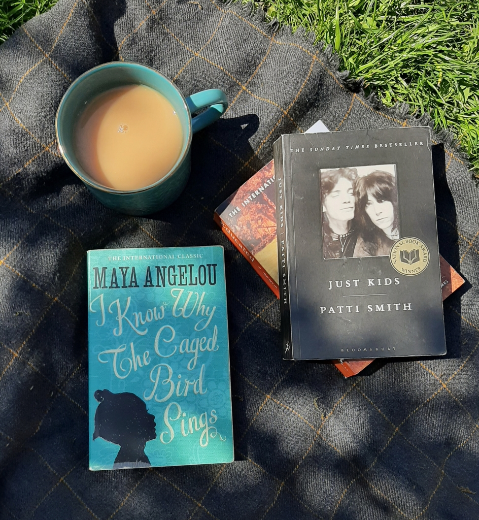 Cup of tea and three books on a grey blanket