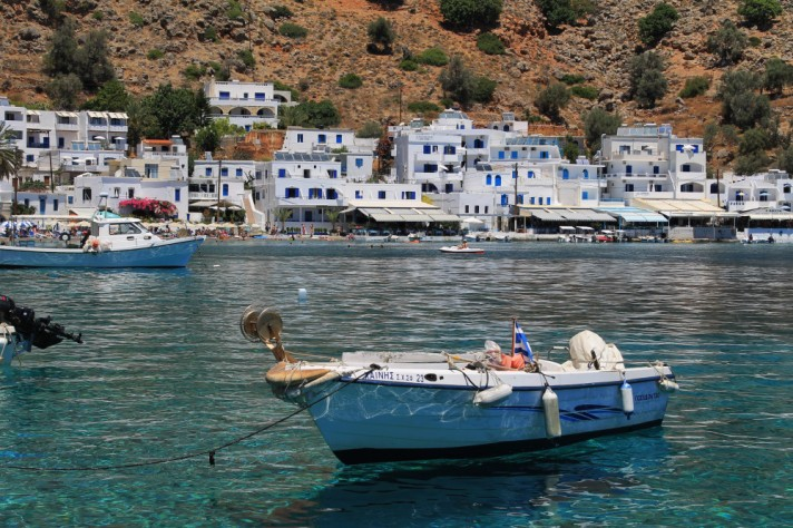 White houses against a sandy hill. Blue water and a white boat in the foreground.