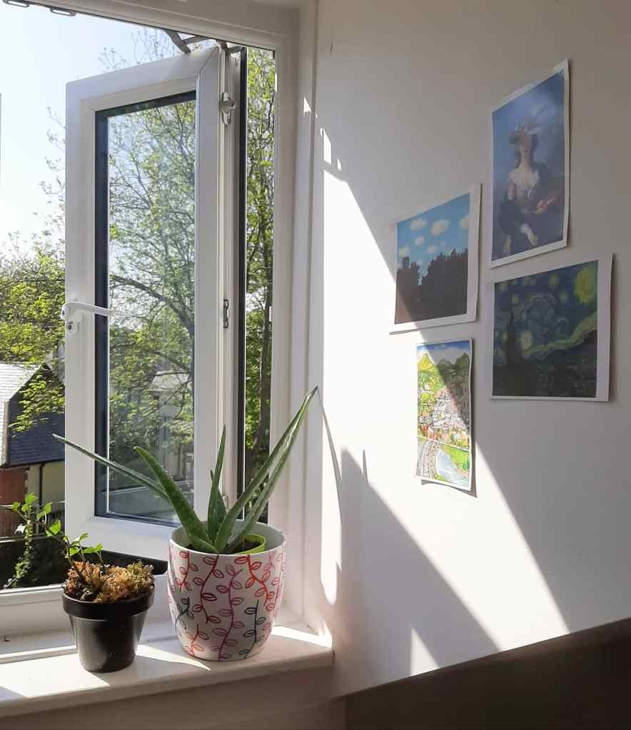An open window with two plants on the sill. There are four pieces of art up on the wall