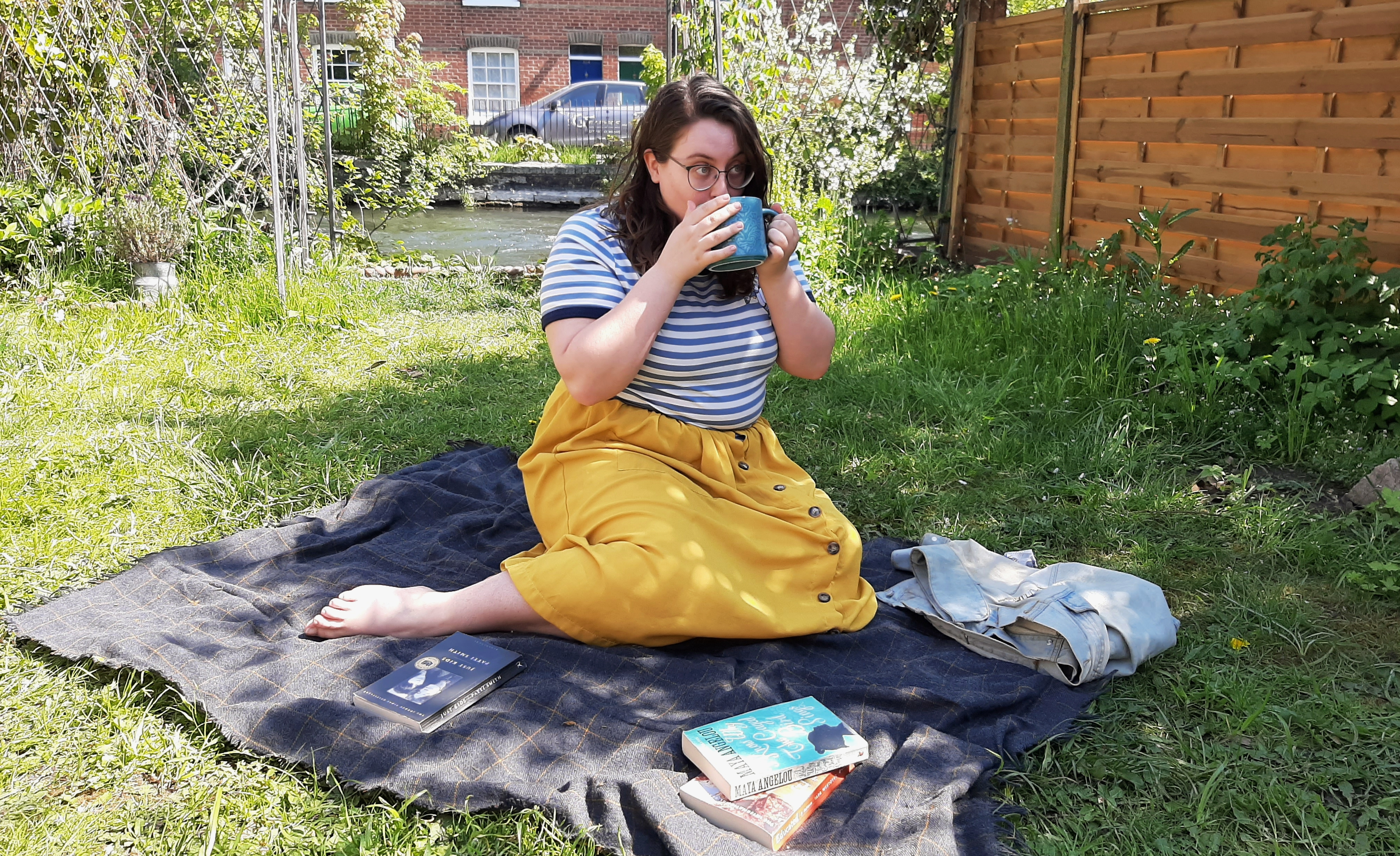 Rosie drinking a mug of tea in her garden, accompanied by some books