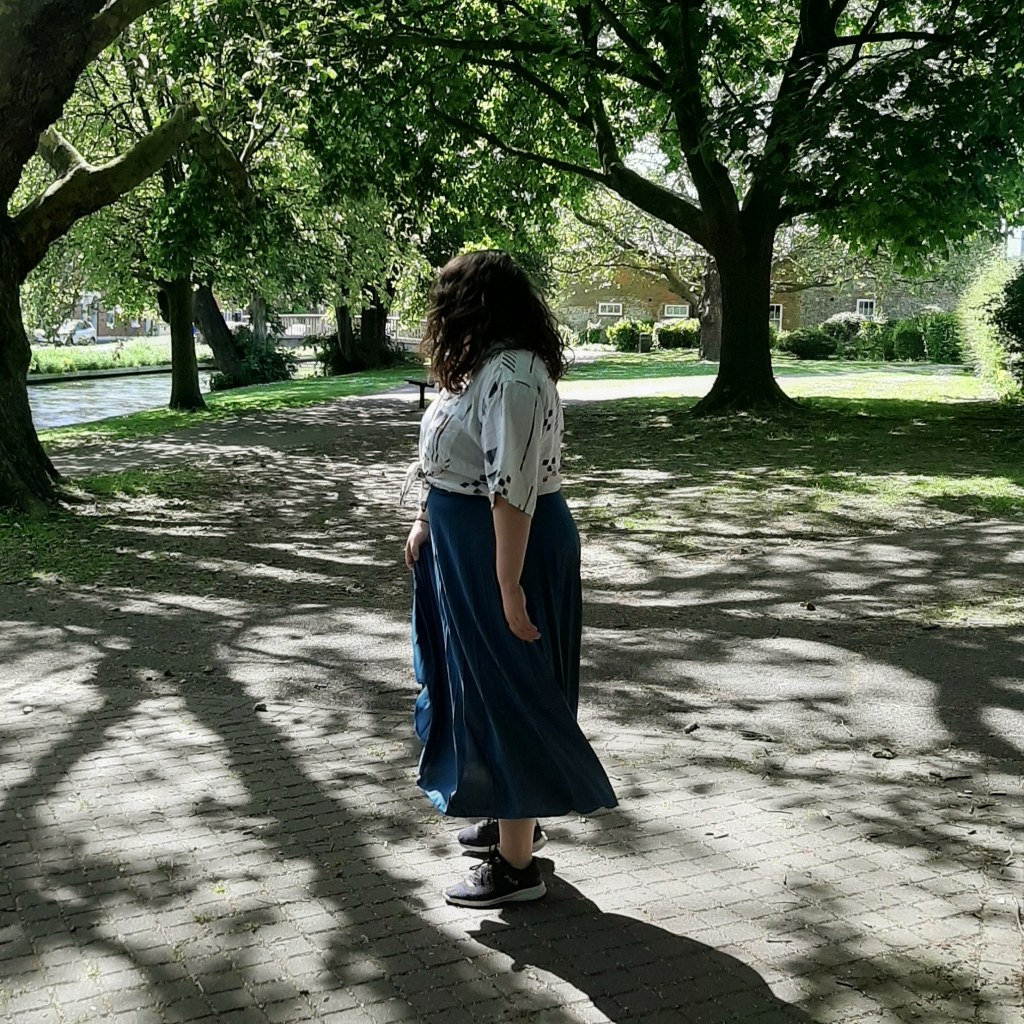 Rosie wearing a blue skirt, and a whiteshirt (with colourful shapes on it). She is looking away from the camera, to a background of green grass and trees