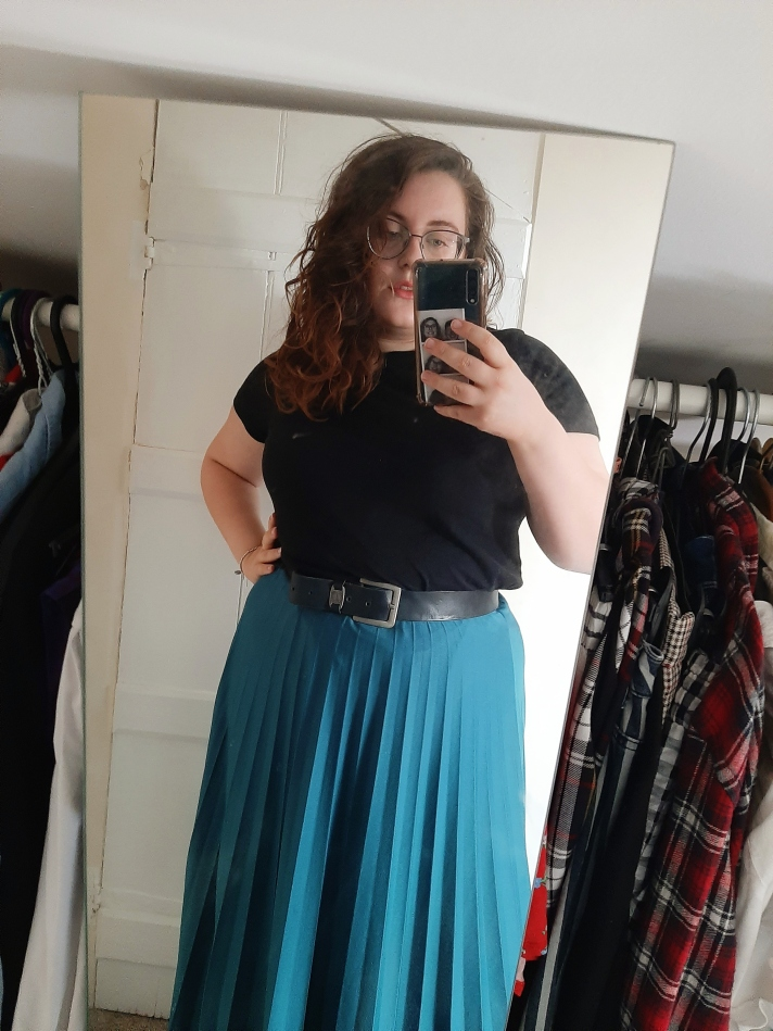 A mirror selfie by Rosie. She is wearing a blue midi skirt, with a thick black belt, and a black tee