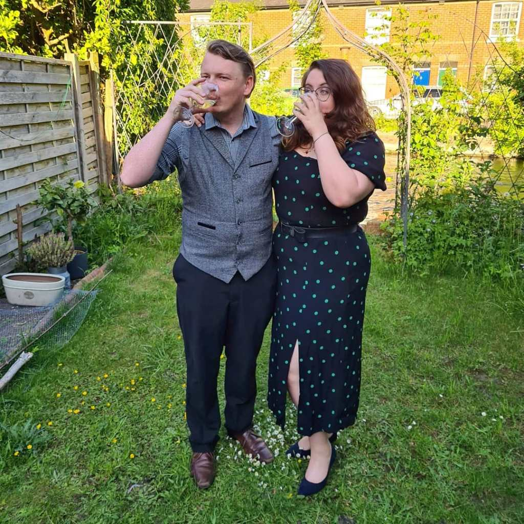 Rory and Rosie in their back garden, sipping wine. Rosie is wearing a black dress with green dots from New Look